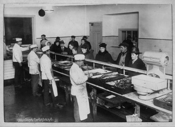 Spanskesyken spredde seg på offentlige møtesteder, som i butikklokaler. Foto fra det kommunale fiskeutsalget på Grønland i 1918. Fotograf: Narve Skarpmoen. Fra arkivet etter Provianteringsrådet (A-20156/Ua/0001/079).