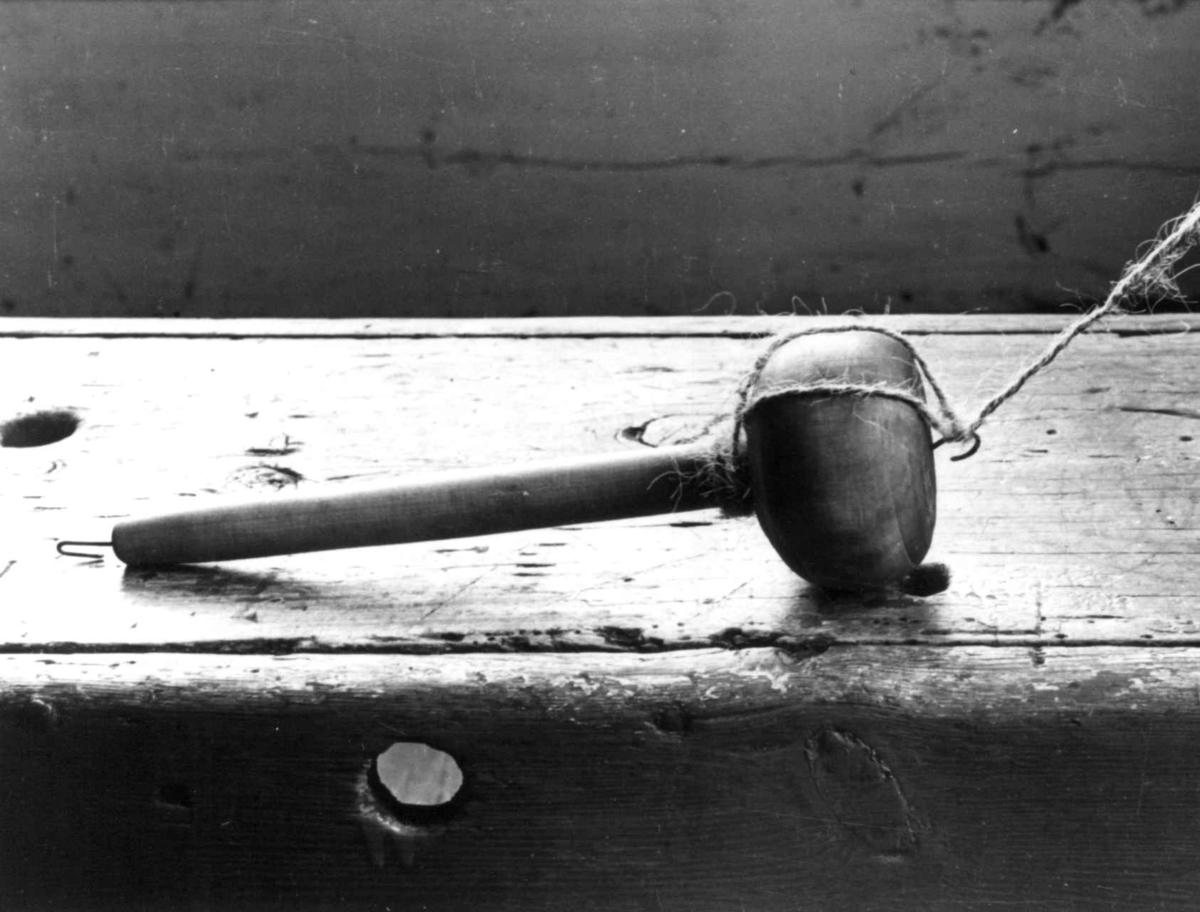 Ragnhild Åvitsland spinner kutagl og grov ull på en liten hjemmelaget håndrokk i tre. Eiken, Hægebostad, Vest-Agder 1941.