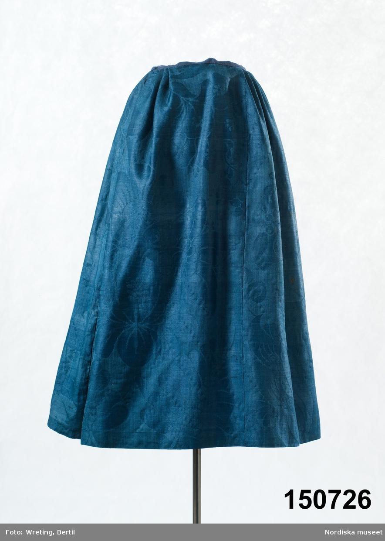 Kjol av mörkblå ylledamast med ett mycket stort blommönster, 5 våder, varav en smalare. Vid ankomst till museet var kjolen uppsprättad till ett slätt tygstycke och har monterats till en kjol inför utställning i den modell som var vanlig i slutet av 1700-talet med slätt framparti 16 cm och därefter smala lagda veck gjorda på ett modernare sätt. Smal midjelinning av mörkblå linnelärft, sprund på höger sida. Skoning har sytts på av vit tapetserarväv. Kjolen är blekt till en mellanblå färg, men den ursprungliga mörkt blå syns på avigan. Handsydd med blå lintråd. Har enligt säljaren tillhört hans hustrus mormor, vars yngsta barn föddes 1844, och troddes därför kjolen kunna vara från 1820-talet. Troligen är den en generation äldre, eftersom dessa damasttyger slutade tillverkas runt 1800. Dessa stormönstrade glättade ylledamasttyger var egentligen avsedda för inredning men blev under 1700-talets andra hälft använda  i bondemiljö som lyxplagg för rika bönder framförallt till bröllopsdräktens kjolar, västar eller livstycken. De finaste vävdes i Norwich i England, men kunde även vävas vid ylleväverier i Stockholm, dock inte lika  glättade. /Berit Eldvik 2011-08-22