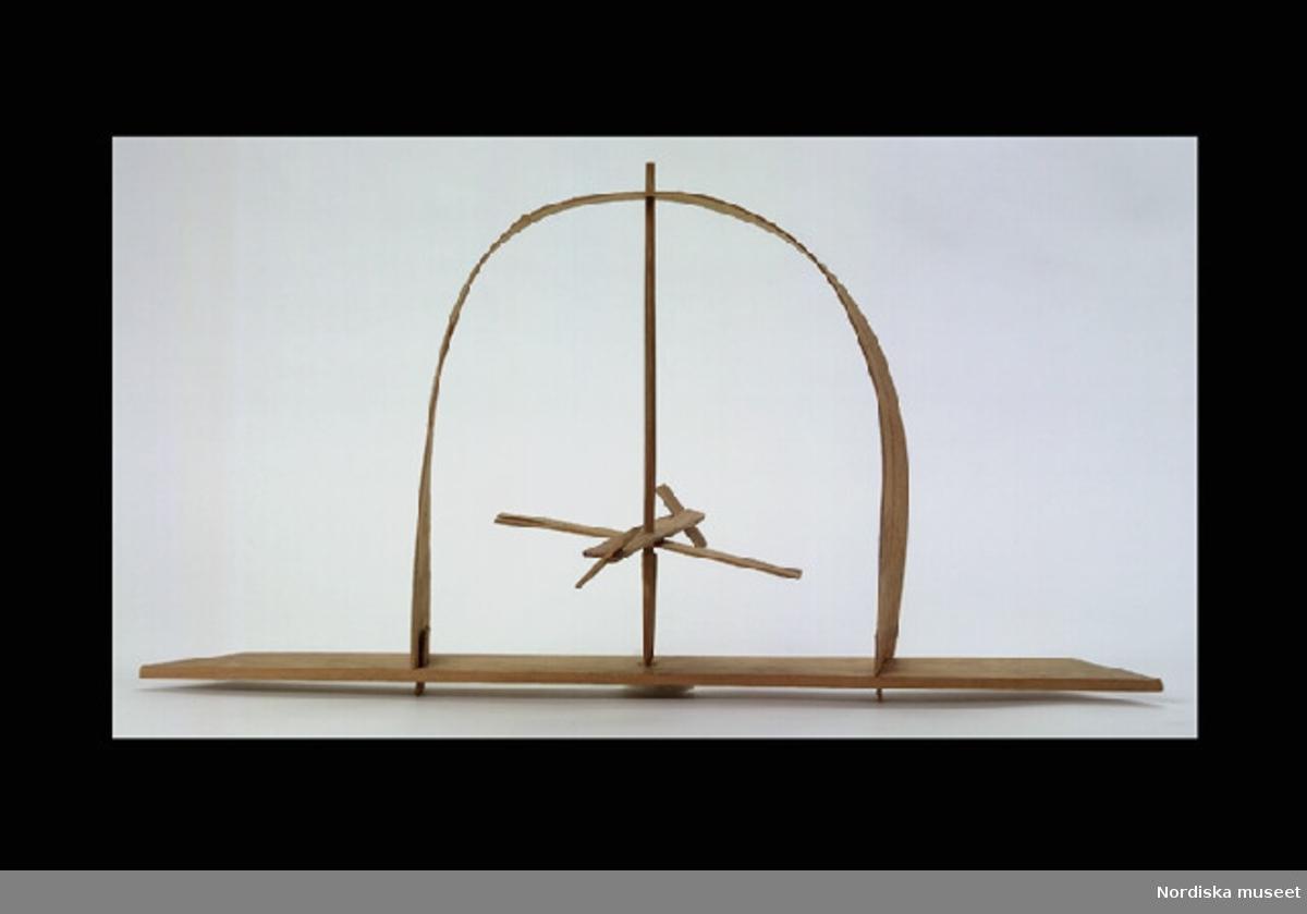 """Katalogkort: """"Spiskvarn, leksak av obehandlat trä. Smalt rektangulärt bottenstycke med snedställda kortändar. Ovantill båge av träspån. Fäst mellan bågen och bottenstycket en rund trästav med 'propeller' mitt på. Propellern består av två korslagda rektangulära trästycken med snedställda träplattor i ändarna (två saknas). Att fästa i spisen så att propellern snurrar av den uppstigande värmen. Tillverkningstid ca 1933. Nytillverkad av givaren (trol. för att visa leksaker från hans barndom. LW sept 1998"""" [= Leif Wallin, inventering Sesam]"""