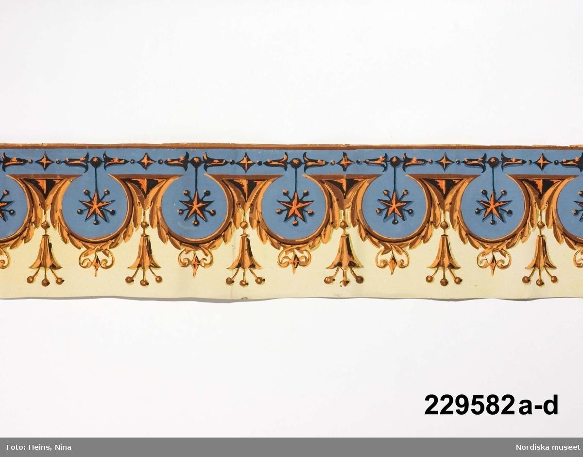 """Huvudliggaren: """"a-d Tapetbård, 4 st., papper med tryckt dekor, komposition med rundlar och hängen eller tofsar i färgerna blågrått med svart och röd dekor samt brunt och svart på gul botten. Stämpel Nr 26. Br. 18 cm. Ingår i en samling tapeter, som sedan långt tillbaka förvarats i museet""""  Utdrag ur bilaga: """"Bilaga till inv nr 229.401 - 230.099 Ovanstående tapetbårder är införda i huvudliggaren med proveniensuppgift att de sedan länge förvarats i Nordiska museet. I flera andra källor har de hänförts till Carl Fredrik Torsselius och hans verkstad i Stockholm och dateras till omkring 1820. Alla tapeter är inte tillverkade av Torsselius, utan några av dem är franska ...""""  Katalogkort: """" Tryckt dekor på papper. H 18 cm. Fond mattgul, kobolt, terra.""""  a) Handskrift samt stämpel på baksidan. Mönstret slutar före bottenfärgen och pappret. Mycket styvt papper. b) Handskrift samt stämpel på baksidan. c) Stämpel på baksidan. d) Stämpel på baksidan. /Cecilia Wallquist 2007-03-21."""