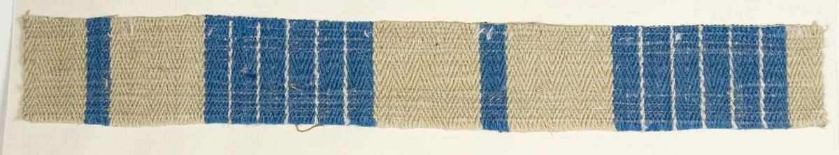 """Vävprov ämnat för bolstervar vävd i spetskypert med bomulls- och lingarn. Beige botten med ränder i blått. Vävprovet är uppklistrat på en kartong i storleken 22 x 28 cm. I övre högra hörnet finns en stämpel """"Uppsala läns hemslöjdsförening"""" och ett handskrivet nummer, """"A.1525""""."""