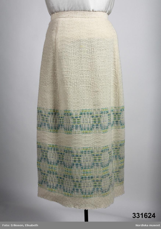 """Vit kjol i tuskaft med flotteringar med grön, turkos, silver bård nertill.  Söm mitt bak, långa insnitt ner till bården (ca. 35 cm) två fram och två bak. Smal linning, hyska och hake, dragkedja bak, hankar i sidan för upphängning. Foder bortklippt, nerkant sicksackad, ofållad. Pappetikett med handskriven text i en hank """"93607"""" på ena sida, andra sidan """"Aureole Stil 5302 Färg St 10 225 400:-"""" (400:- överstruket) /Magdalena Fick 2011-11-14"""