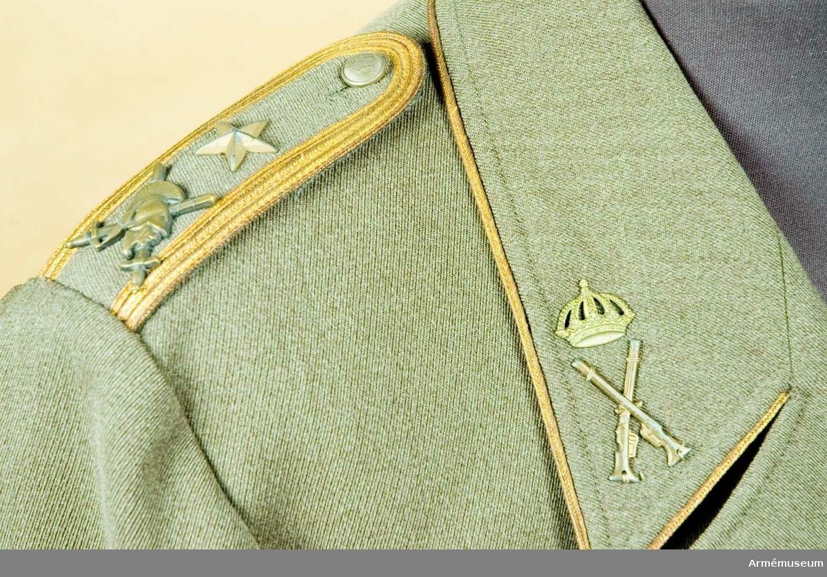 Stl C 146. Till fältuniform m/1939, enradig utan livsöm.  Av gråbrungrön yllediagonal. Mjukt, nedvikt krage som går att högknäppa. Utvändiga bröstfickor med raka ficklock och bälgar, försedda med liten knapp m/1939 och motsvarande knapphål i ficklocken. Utvändiga sidfickor med raka ficklock och bälgar. Skarpa hörn. Innerfickor på båda sidor övre framstyckena. Sprund i ryggen. Axelklaffar m/1939 med krigshögskolans emblem och en st majorsstjärna. Liten knapp för knäppning av klaffen, (tre kronor). Slagen: Avståndet från crochévinkeln till slagspetsen är 60 mm. Vänstra slaget försett med knapphål för att kunna knäppas upp genom knappen under kragen (liten). Försedd med rygg och sidsömmar. Två delvis tillsydda veck i ryggen som kan sprättas upp vid behov. Insyning på frampartiet. Rocken är uppvikt, försedd med foder. Hög underärm för större rörelsefrihet. Rocken är försedd med släpband för svärdsorden. Slagen försedda med tjänstetecken för regementsofficer = korslagda gevär för infanteriet under krona för reg.officer.