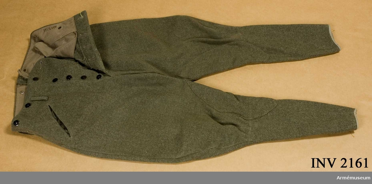 Stl 50. Av gråbrungrön yllediagonal med julpknäppning och knappar i midjan för hängslen. Fickor i sidsömmen och två bak, knäppta med byxknapp. Vid insidan av byxbenens nederkant knapp för fastsättning av resår, att spännas under skon.