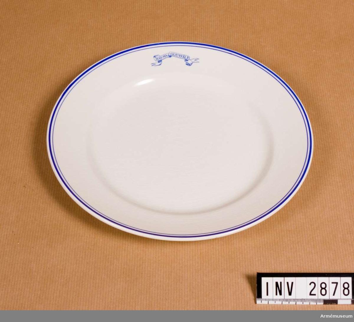 """Vitt porslin med blå dekor; runt ytterkanten en något kraftigare rand än den innanför. Emblem i form av banderoll med text """"MARMA SKJUTFÄLT"""". Undersidan märkt """"Gustavsberg 1718 R2"""". Har använts vid off.mässen, Marma läger. Porslinet har tillh. A 1 och har förmodligen anskaffats i början av 1930-talet som ersättning för porslin som blev förstört när mässen brann ner feb 1930.  Samhörande nr är 2625-2630, 2876-2881 (2876-2881)."""