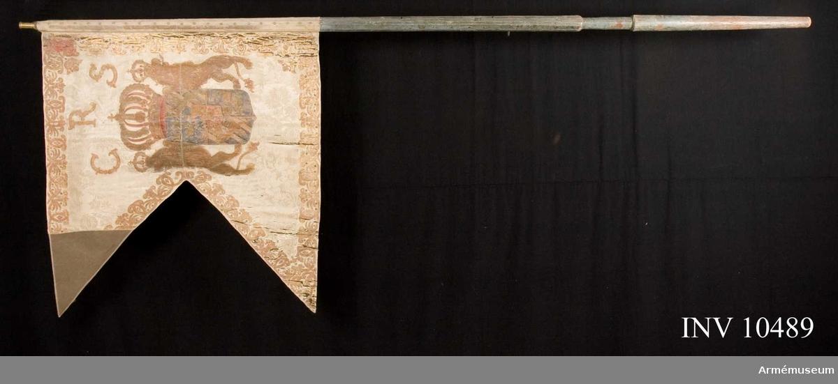 Grupp B I.  Av vit sidendamast varå målats lika å båda sidor svenska riksvapnet under pfalziska huset i guld, silver och färger. Kronan med rött innerfoder även å byglarna. Sköldhållarna är dubbelkransade och krönta med slutna kungliga kronor. I båge  över vapnet i guld C R S (å yttre sidan omvänt). Längs kanten bård i guld och silver av kronor, palmkvistar och ornament liknande dubbla C å bården i övre, inre hörnet Skånes sköldemärke, rött griphuvud krönt med öppen, gyllene krona. Fäst med tre vita sidenband och förgyllda spikar.