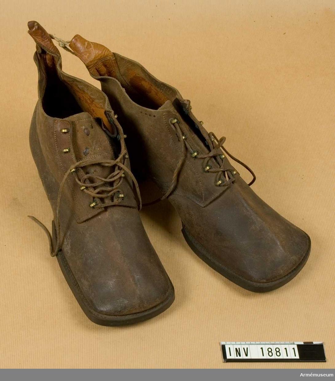 """Av grovt, brunt läder med inskärning på framsidan och med 5 par hakar för att snöra skorna. Sulan betäckt med spikar och klacken med järnbeslag. På sulan finns nummer """"4"""", på kängans innersida finns stämplar """"78"""" - med krona ovanpå (möjligen år 1878). Andra stämplar oläsliga."""