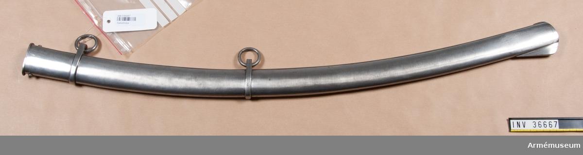 """Grupp D II.  Baljan är helt av järn och har två ringliknande beslag som kvarhåller de båda koppelringarna. På utsidan av det övre beslaget är numret 13 inslagen. På en vid nedre koppelringen fäst lapp finns konungens generaladjutantsexpeditions sigill i rött lack och påskriften """"år 1815"""". Kallas i Modellsalens reversal """"Sabel med balja, svenska, artilleri, st. 1"""""""