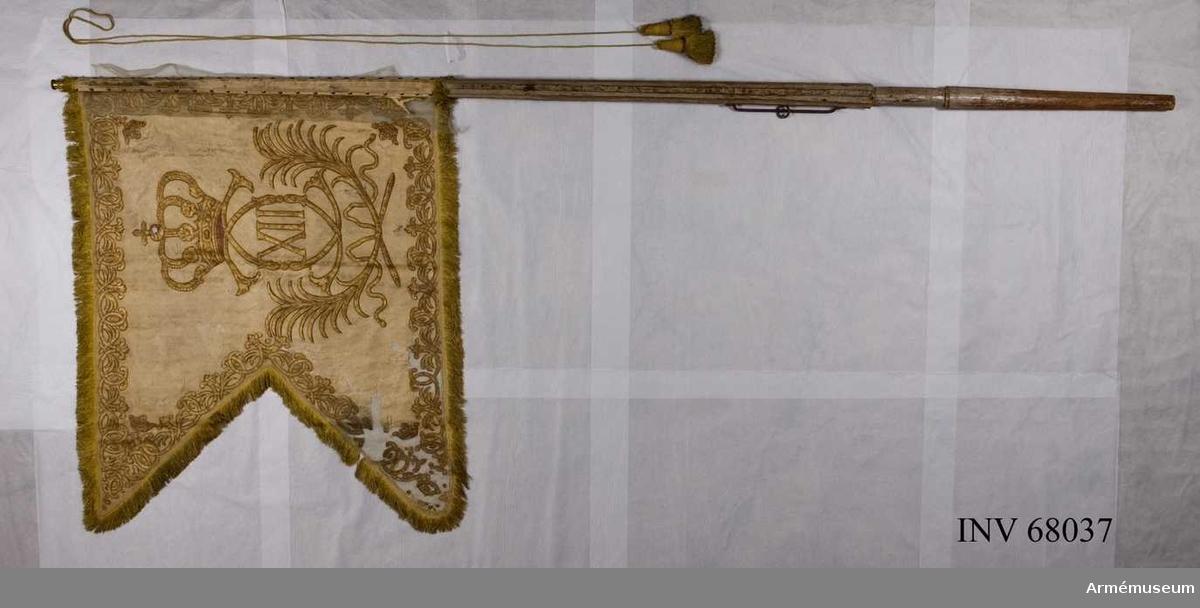 Duk: Tillverkad av enkel vit sidendamast. Tvåtungad, sydd av två horisontella våder. Kantad med gul silkesfrans. Fäst vid stången med tre rader tennlickor på vita sidenband.  Dekor: Målat omvänt lika på båda sidor, Karl XII:s namnchiffer, dubbelt C under sluten rödfodrad krona, inneslutande XII. Däromkring två lyrformigt böjda palmkvistar, längs kanten en bård av palmkvistar och dubbla C liknande ornament, samt i hörnen små öppna kronor. Målat med konturer i rödbrunt.  Stång: Tillverkad av vitmålad furu. Kannelerad ovanför greppet.   Holk av förgylld mässing, fastsatt med tre spikar.  Banderoller: Tillverkad av gult silke, flätade med två tofsar som också är tillverkade av gult silke.