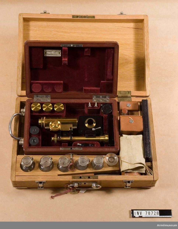 """Grupp  I III. Träväska med lås, märkt i locket: """"Ernst Leitz, Vertr. Frz. Bergmann. Berlin N.W. Luisenst 45"""". Inredd med fack innehållande glasflaskor, slaktkniv, mikroskop, objektsglas av olika storlekar ett läderetui (bindtyg) med pincett, dissektionskniv, saxar samt febertermometer. Mikroskopet ligger i en egen väska av läder som är märkt i locket """"Ernst Leitz, Agent Axel Lundqvist, Stockholm, Hantverkaregatan 15"""".  KT 2011-10-31"""