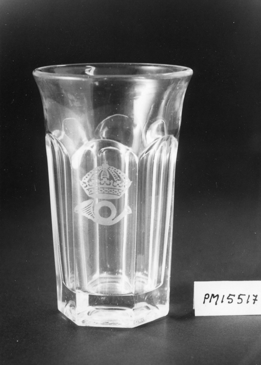 Dricksglas av ofärgat glas, sexkantigt, men runt upptill. Påsidan ett krönt posthorn av 1912 års modell.