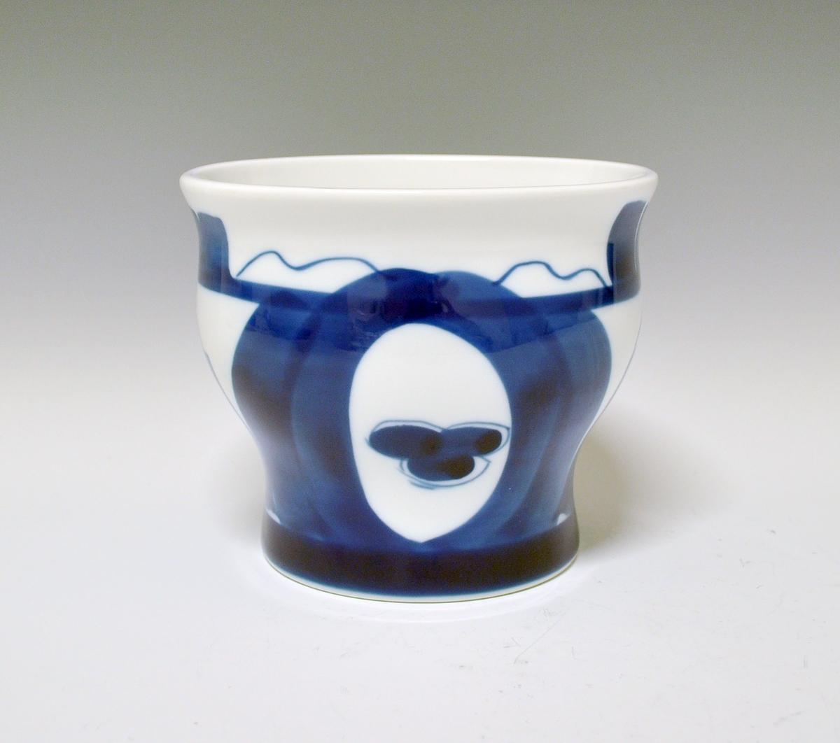 Vase i porselen. Bølget form, sirkelformet fot og oval åpning på toppen. Hvit glasur. Blå underglasurdekor. Kunstner: Unni M. Johnsen.
