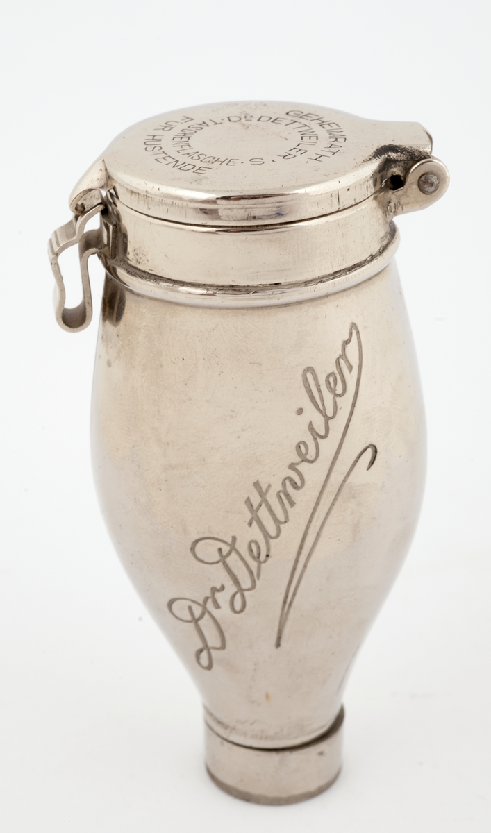 Flaskeformet, oval beholder av metall med hengslet lokk. Lukkeanordning oppe, skrukork nede. I lokket er gravert inn  informasjon om bruk av beholderen. På beholderens to flate sider er gravert inn et legenavn.
