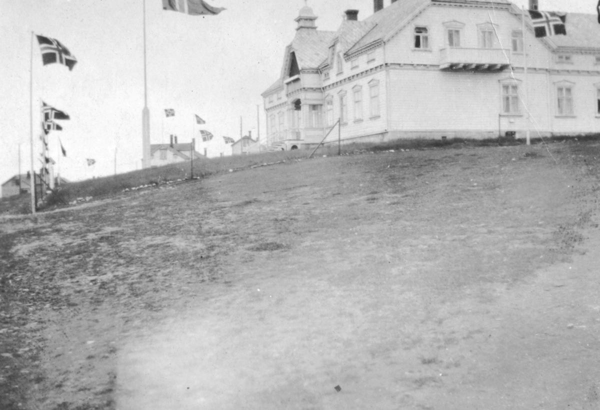 Motiv av Fylkesmannsgården i Vadsø. Pyntet med flagg i anledningen Kong Haakons besøk i 1922