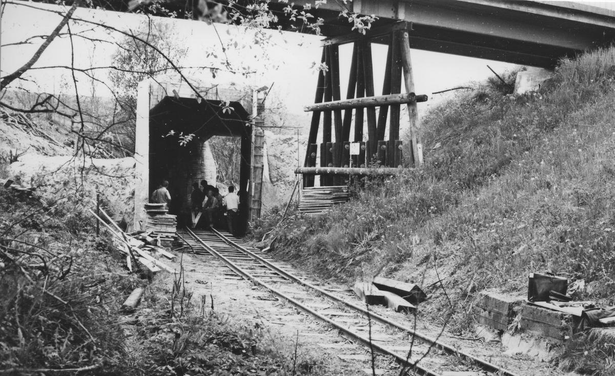 Tønsberg tunnel (kulvert) er ferdig støpt og sporleggingen gjennom tunnelen påbegynt. Fundamentet til den ganle riksvegbroen over Urskog-Hølandsbanen i forgrunnen. Broen ble revet i 1968.