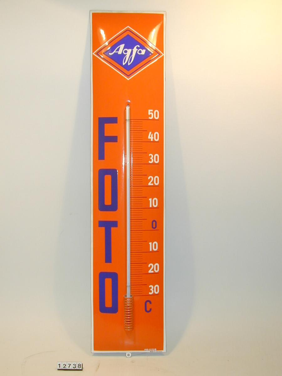 Agfa foto reklameskilt kombinert med termometer. Form: Rektangulært tverrsnitt, høysmal. svakt buet front.
