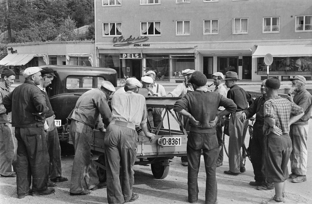 Gruppe menn ved tilhenger med kappsag. Leiret, Elverum.