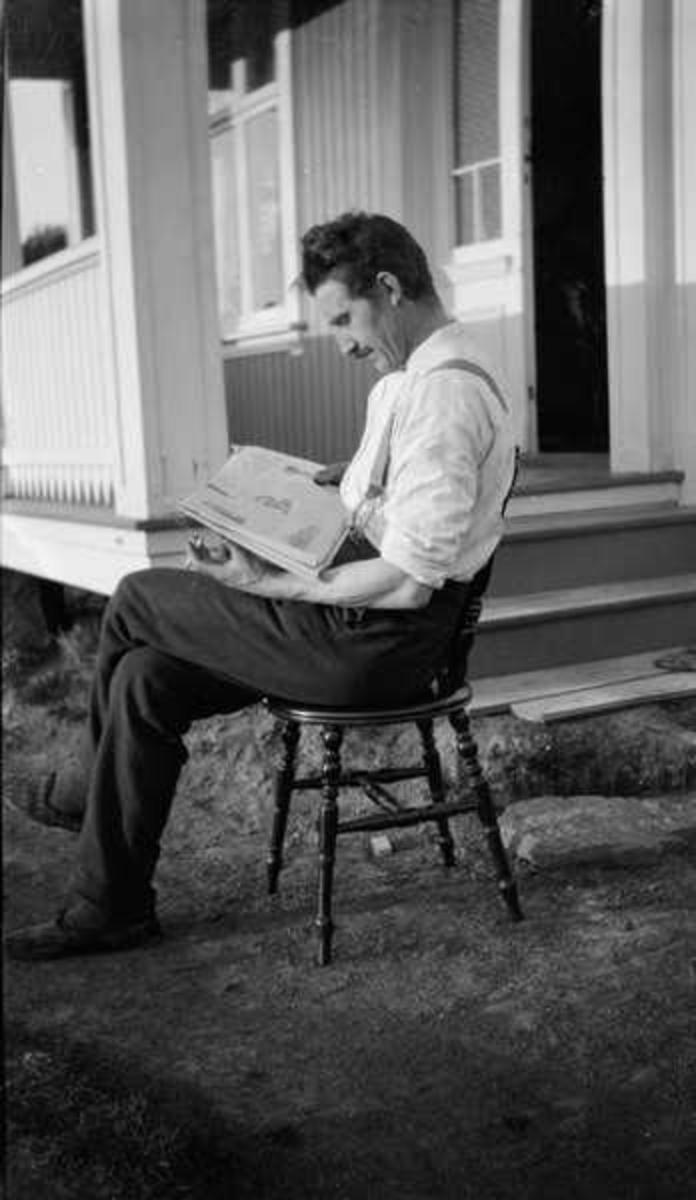 Mann sitter ute på en stol og leser. Museum Nord