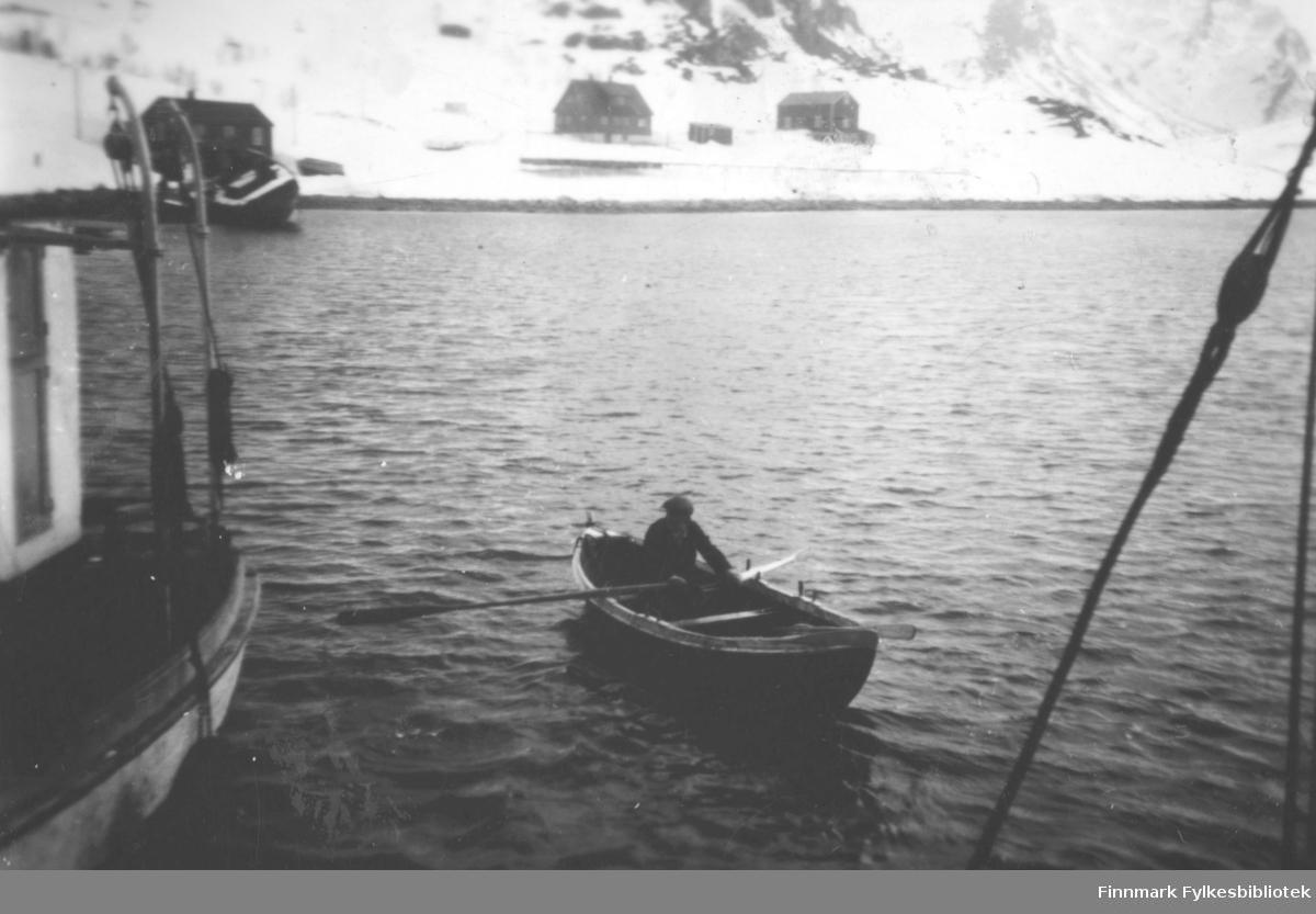 Gården til Evald Valen sett fra sjøen. Til venstre ligger Sara? sin bolig. Nedenfor huset ligger en båt i fjæra. På vannet er det en mann som ror inn mot land. En del av en båt ses helt i venstrekanten av bildet. Snøen ligger på bakken
