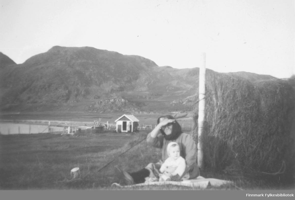 Anna Andersen sammen med et barnebarn. De sitter på bakken ved siden av en hesje, ute på et jorde. Det henger gress til tørking på hesjen. Naustet som ses ved vannet, tilhører henne og mannen Aanet Anderssen. I bakgrunnen er det fjell