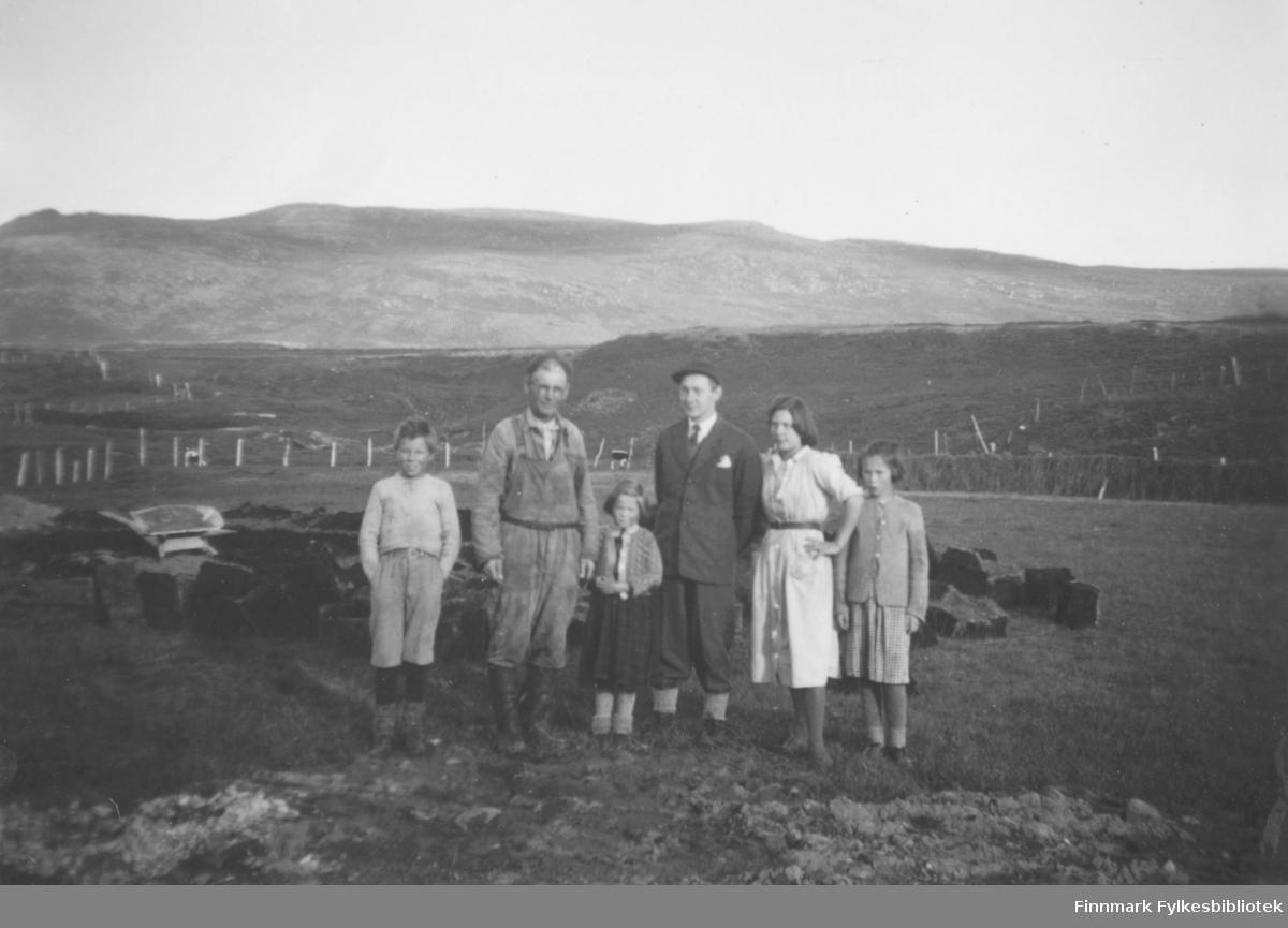 Torvstikking i Kokelv. Fra venstre står Arvid Nilsen som er sønn til Anders Nilsen som står ved siden av. Mannen med slips er lærer Anders Ydstie. De tre jentene er hans døtre. May Ydstie står i midten. Fra høyre står Eli Ydstie, og Ragna Ydstie. På jordet ligger det torv. Det henger høy på hesjer til høyre i bildet. Området er inngjerdet