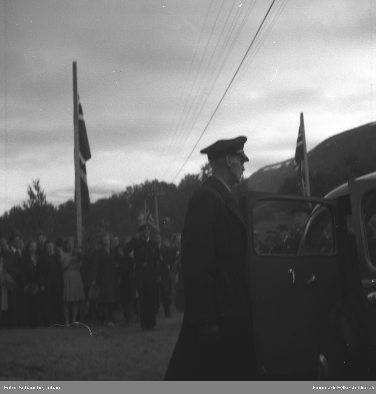 Kongebesøk i 1946:  Kong Haakon VII besøker Tana. Kong Haakon går inn i bilen etter besøket. Bak bilen står folkemengde med flagger.