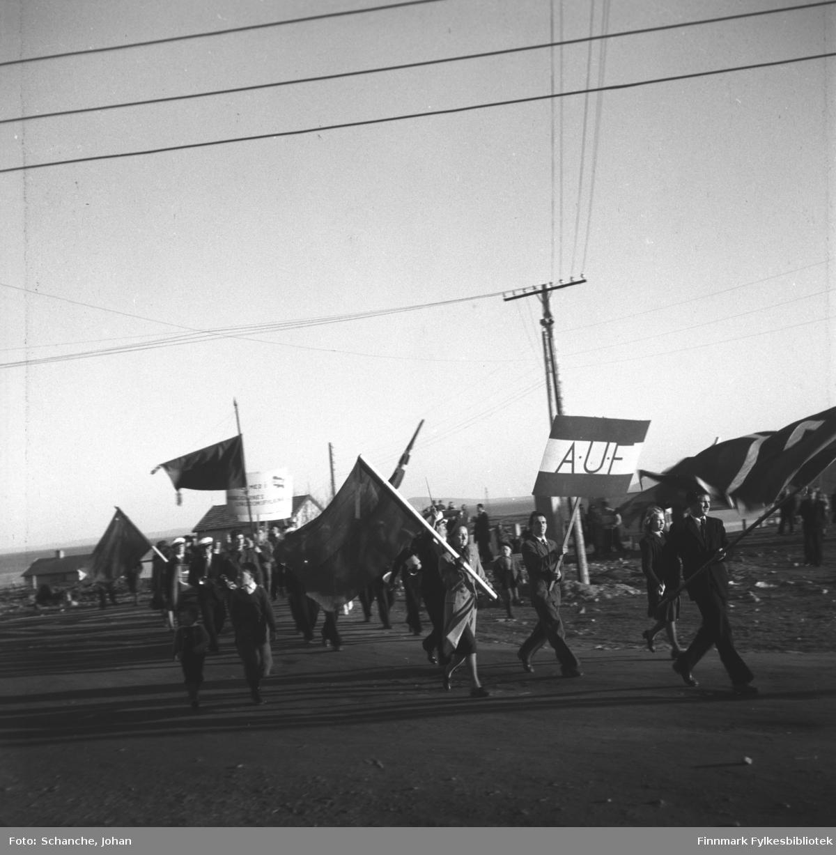1. mai tog fotografert i Vadsø -48. Folketoget går langs gata med plakater og flagger. I en av plakatene står  AUF. Dagen er solig og fin.
