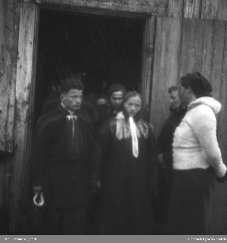 Menn og kvinner i samedrakt kommer ut av Polmak kirke påsken -46.  Bildet er tatt ved døråpningen, to kvinner står ved paret i sametrakt som komer ut av kirka. Muligens brudepar?