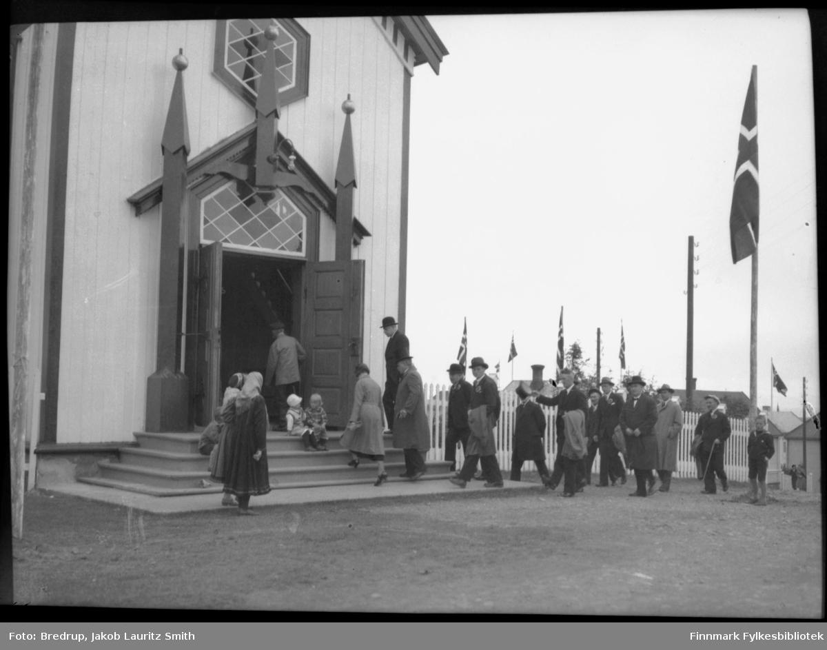 Byjubileet 1933 - Vadsøs 100-årsjubileum. Formannskap og bystyret i Vadsø ankommer festgudstjenesten 22.7.1933.  Det er flest menn i hatter og med kokarde på brystet, men også en kvinne.  I kirketrappa sitter to barn, og et par kvinner står som tislkuere, den ene i samekofte.  Det flagges i byen.  Bildet gir et godt inntrykk av kirkedøra og inngangspartiet på Vadsø kirke
