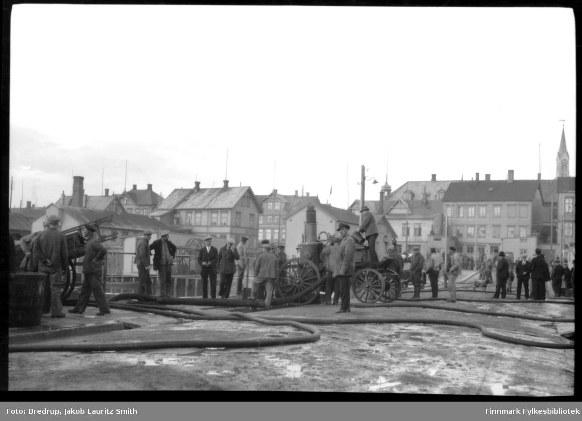 Brannvesenet i aksjon på Valen i Vardø.  Masse folk har samlet seg for å se på.  Sakkyndig samler mennene seg rundt brannutstyret.  Midt i bildet en damsprøyte, vi ser brannslanger og annet utstyr.