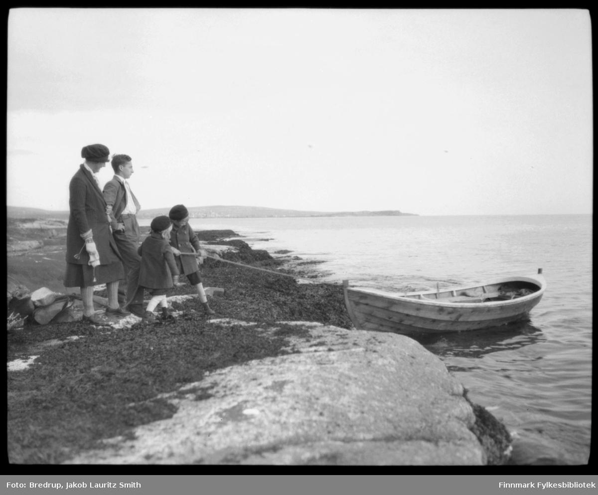 En familie med to barn fortøyer en robåt, antakelig på Vadsøya.  Kvinnen er Hildur Bredrup. Barna er Trygve Bredrup, og antakelig Ruth Bredrup Handal.  Vi antar det er Ruth, pga aldersforsskjellen.  Mannen er ukjent, Hildur Bredrups bror?