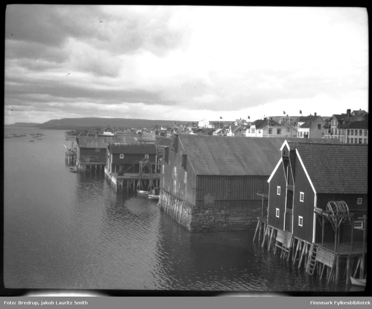 Vadsø havn fotografert mot vest.  Man ser pakkhus, kaier, havna med båter, bebyggelsen i Havnegata.  Bildet er tatt 17. mai 1933, det flagges i byen.