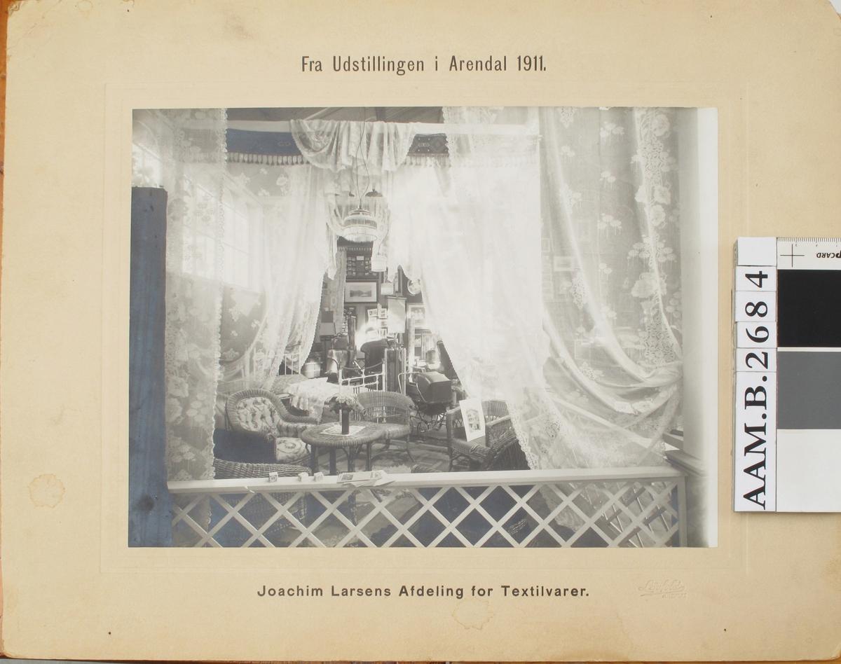 Utstilling, Joachim Larsens stand i Arendalsutstillingen 1911 , interiør med kurvstoler, bord, tekstiler m.m.