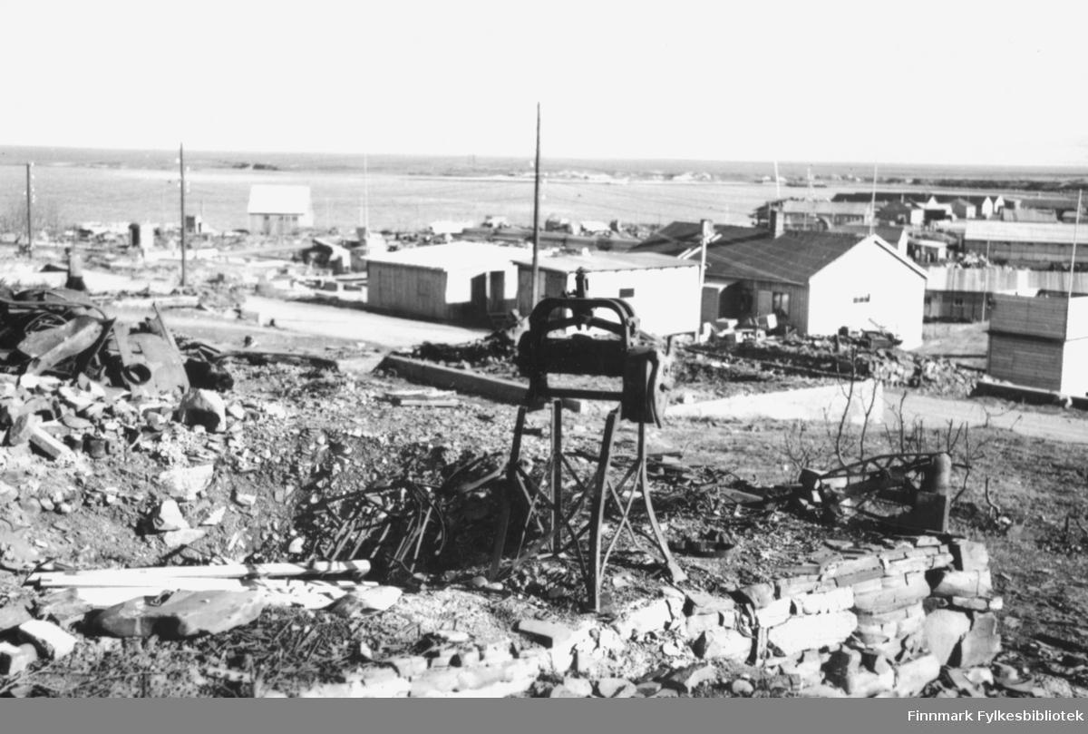 Motiv fra Vadsø sentrum etter andre verdenskrig. Mye av sentrum lå i ruiner, men gjenreisningen var startet, og man ser i bakgrunnen at flere brakker allerede er bygd. I forgrunnen på restene av en grunnmur står en klesrulle. Utsikt ned mot havet og Vadsøya