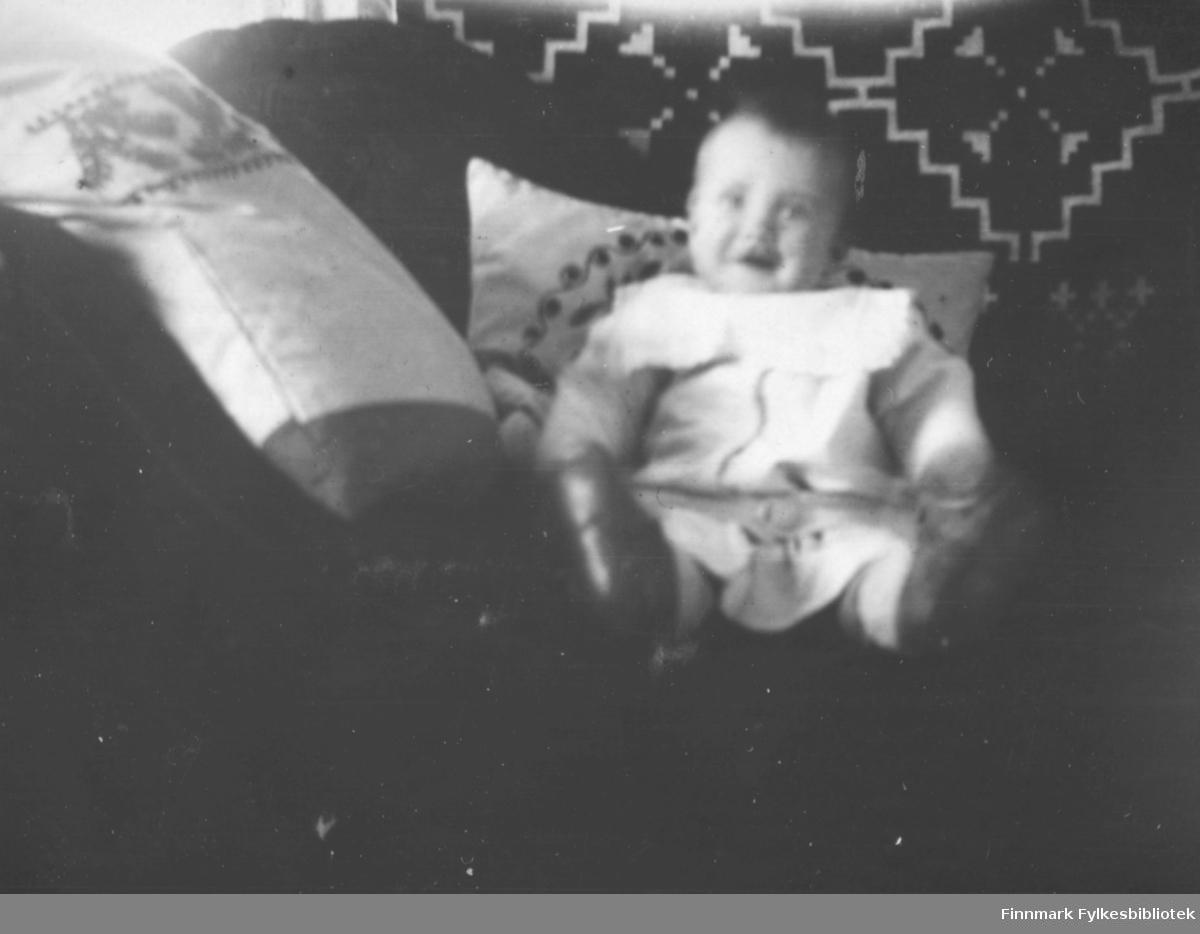 En liten gutt, Einar med ukjent etternavn, sitter i en sofa med vakre broderte puter