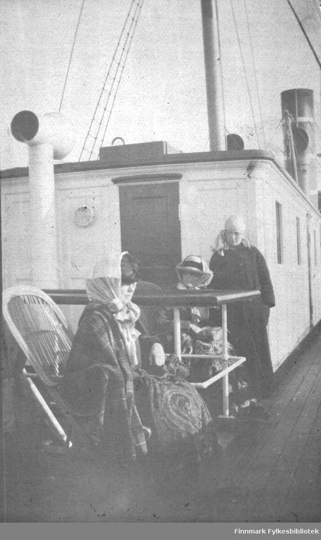 Tre damer fotografert på dekk på en båt. Båten kan være 'D/S Sirius', som trafikkerte norskekysten første halvdelen av 1900-tallet.