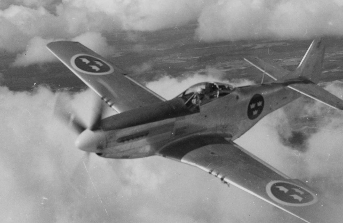 Flygplan J 26 ur svenska flygvapnet flyger över moln.