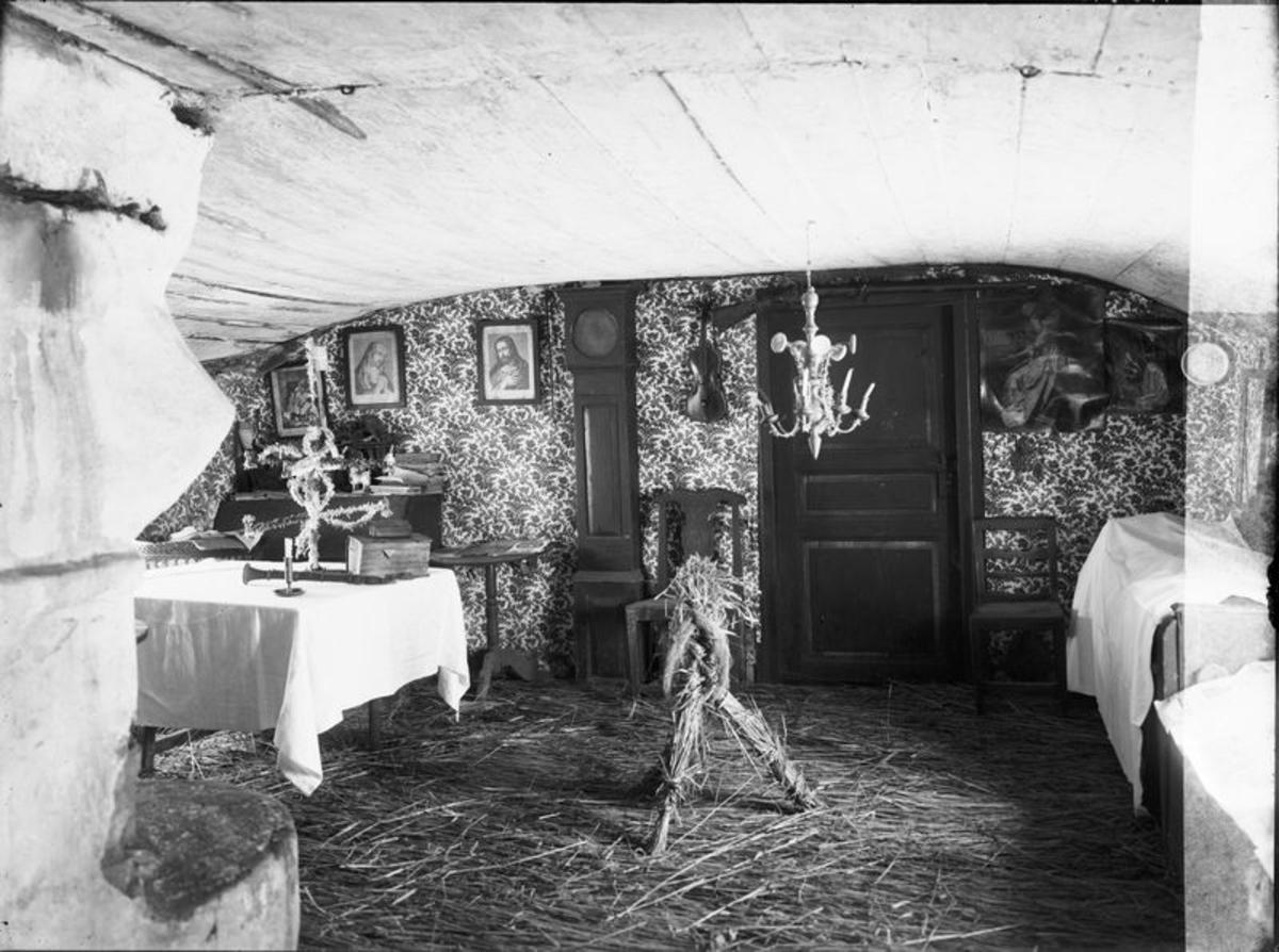 Interiör av gamla stugan med julhalm på golvet. I förgrunden Julbocken. Stugan flyttades på 1920-talet till Bitterna.  Mellomgården  Hudene