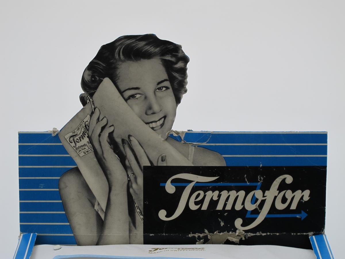 Kvinne som holder en varmepute , delvis foran ansiktet.