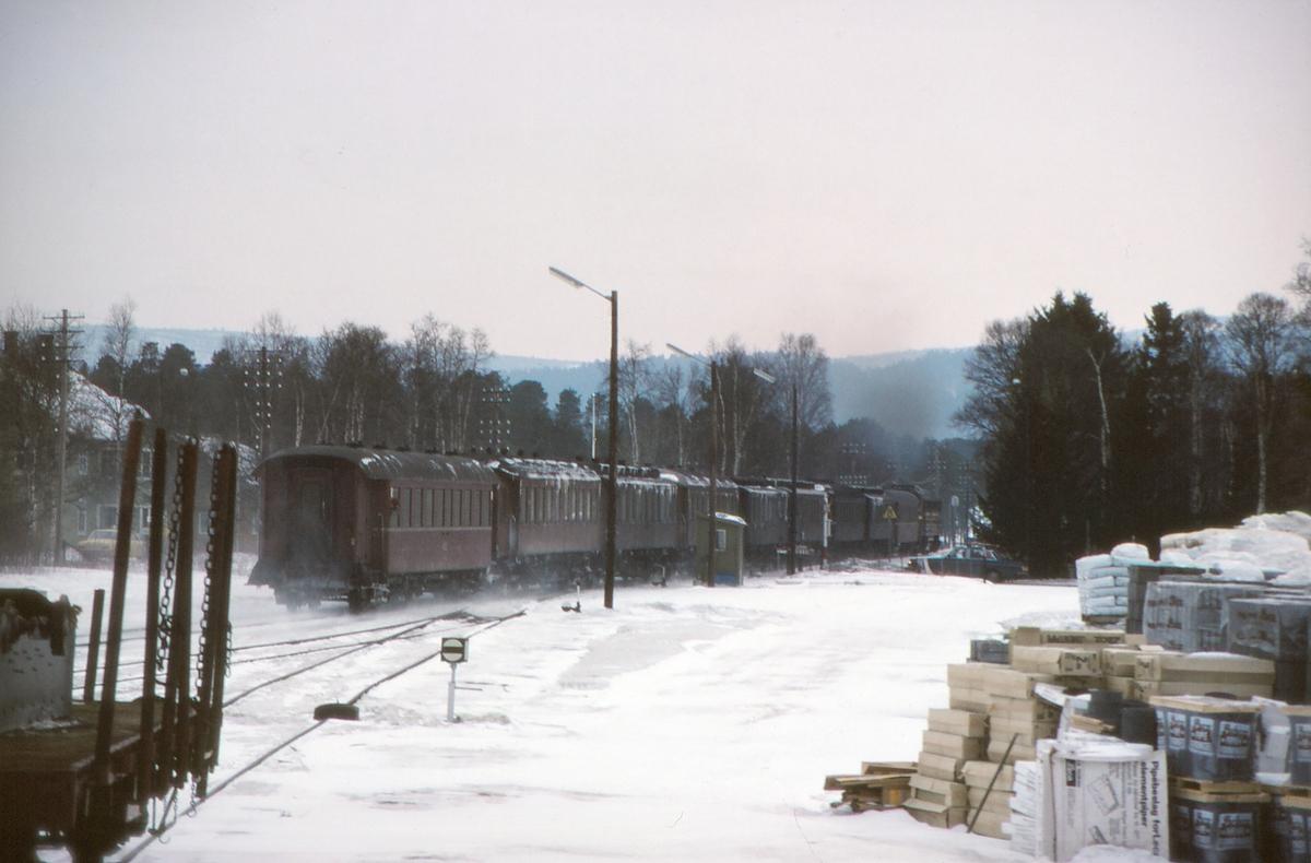Ekstra tomtog Røros - Oslo kjører ut fra Os stasjon, Os i Østerdalen. Materiell fra ekstra persontog Oslo - Røros (påsketog palmelørdag). NSB dieselelektrisk lokomotiv Di 3 625 med to stålvogner type B1 og teakvogner av forskjellige typer.