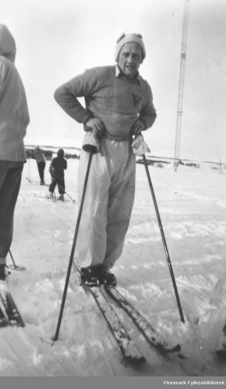 Fritz Ebeltoft etter bedriftsstafettløp på ski i Vadsø ca. 1950-1952. Her hviler han på skistavene