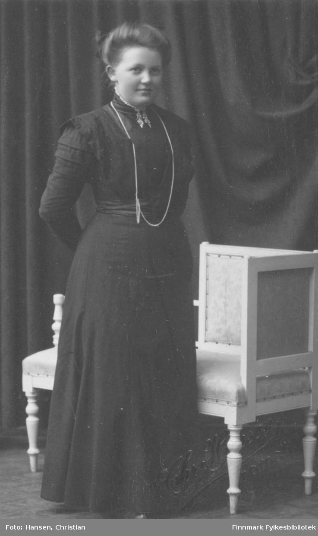 Portrett av ukjent kvinne. Hun er kledd i en mørk elegant kjole og har på seg smykker. Rundt halsen henger det et langt smykke som når henne ned til midjen. På kjolens halsstykke er det blitt festet en vakker brosje. Brosjen ser ut som om det kan være et samisk verk. Kvinnen poserer foran en sofa/stol.