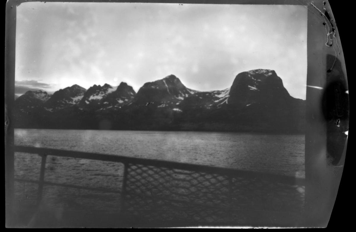 Bildet er tatt ombord eller fra et dampskip /hurtigrute. Bare gjerdet vises fra selve båten. På bildet fjorden og fjellene: fjellformasjonen 'De syv søstre' i Alstahaug kommune