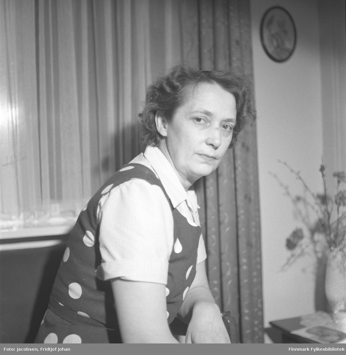 Aase Randi Jacobsen fotografert i en stue. Hun har en kortermet, lys bluse og en mørkere kjole eller et forkle med runde prikker. Gardiner henger foran vinduet bak henne og et fotografi i en avrund ramme henger på veggen oppe til høyre. Et lite bord står på gulvet nede til høyre. En vase med noen blomster i står oppå.