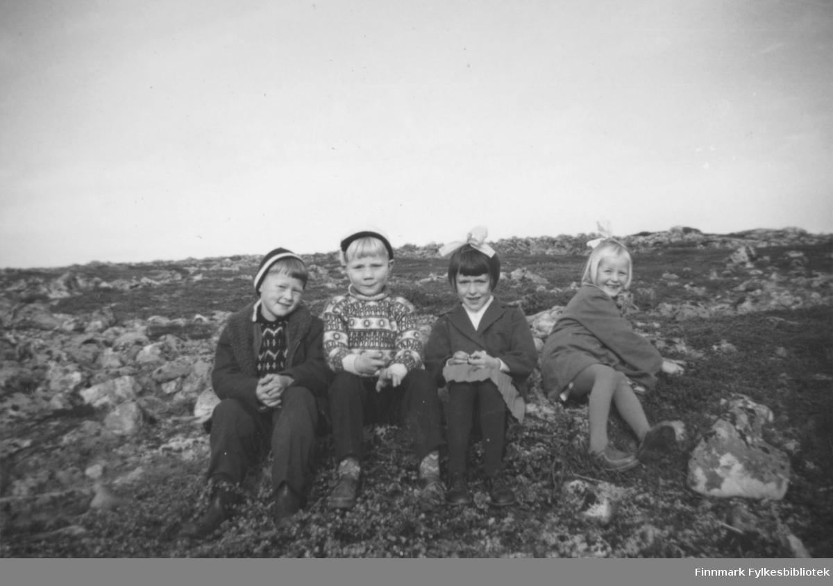 1. Klasse ved Krampenes skole 1962-63. Barna sitter på bakken blant store stener. Fra venstre til høyre: Jon Arne pleym, Ronny Ananiassen, Svanhild Rushfeldt og Ellinor Stock.Jentene har sløyfer på hodet mens guttene er kledd i luer. Jon og Ronny har på seg gensere.