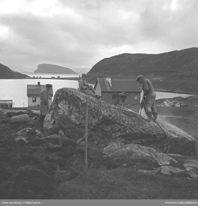 Arne Nakken står med trykkluftbor på en stor stein på eiendommen sin i Rypefjord. En gutt sitter oppå steinen og en mann står i lys frakk til venstre for steinen. To hus og taket på et tredje står litt lengre ned og en haug med materialer ligger i terrenget til høyre på bildet. Havna i Rypefjord  ses midt på bildet og fjellet til høyre er Rypefjell. Helt til høyre på bildet står Rypklubben med Rypklubbeidet mellom de to fjellene. Øya Håja ses i bakgrunnen, over Rypklubbeidet.