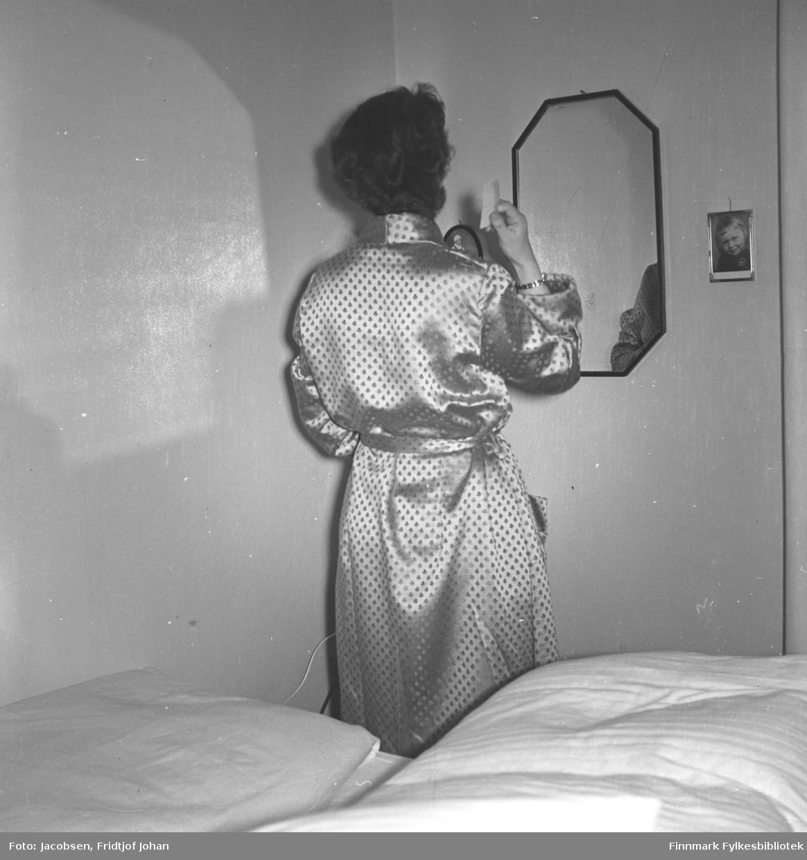 Aase Jacobsen på soverommet i sitt hjem i Storvannsveien. Hun står med ryggen mot kamera og har en lys nattkjole med priker på seg. Hun har et armbånd på sitt høyre håndledd og holder noe i handa. Senga med en lys pute og dyne er rett bak henne og på veggen foran henne henger et speil med sort ramme. Bildet ved siden av speilet viser Ragnhild Jacobsen, niesen hennes.