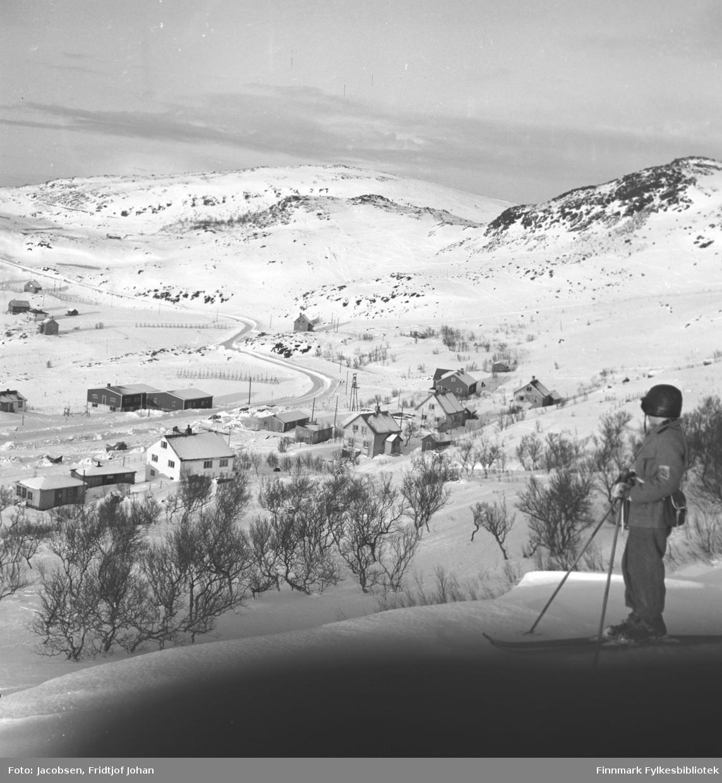 Arne Jacobsen på skitur ovenfor Bjørkåsen i Rypefjord. Han har ganske mørke turklær og skinnlue på seg. Noen trær står i bakken litt nedenfor Arne. Noen hus er kommet opp i Rypefjorden. Det store, hvite huset nede til venstre på bildet er Arne Nakkens hus med Fridtjof Jacobsens hytte ved siden av. Fjordaveien slynger seg i terrenget og går opp mot Jansvannet/Storsvingen til venstre på bildet. Noen snøskjermer står i terrenget.