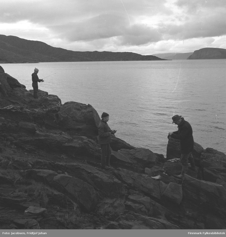 Jacobsens på fisketur til Strømsnes utenfor Hammerfest/Rypefjord. Lengst fra kamera står Ivar Jacobsen i mørke klær og lys topplue med en fiskestang i hendene. I midten stå Arne Jacobsen, også han med en fiskestang i hendene. Han har mørke klær og en mørk topplue på hodet. Til høyre står Fridtjof Jacobsen iført mørke klær og hatt på hodet. Det lange neset på andre siden er Hundneset på Seiland og helt til høyre på bildet ses øya Håja. Sjøen ligger blikkstille, men en overskyet sommerdag.